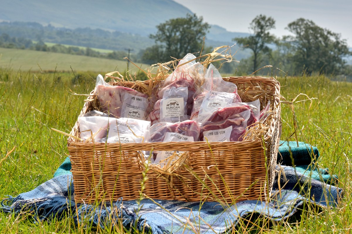 Whole box of sustainably farmed, local produce - our naturally produced lamb in basket. With view to Dumgoyne.